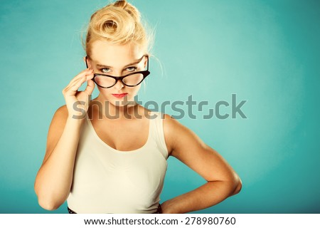 Optometrist, oculist and ophthalmologist concept. Young blonde retro pin up angry woman with eyeglasses in studio. Retro and vintage photo.