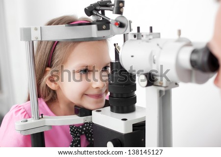 Optometrist performing visual field test of young girl