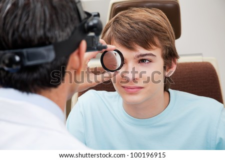 Optometrist taking a closer look at pupil while performing dilated retinal exam