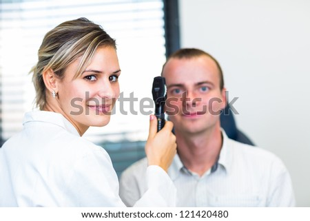 Optometry concept - handsome young man having her eyes examined by an eye doctor