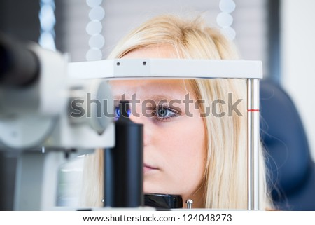 Optometry concept pretty young female patient having her eyes examined by an eye doctor color toned image shallow DOF