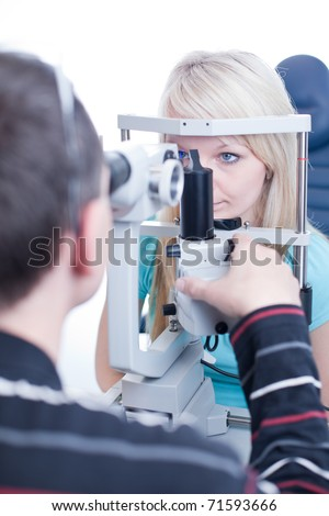 optometry concept - pretty young female patient having her eyes examined by an eye doctor (color toned image; shallow DOF)