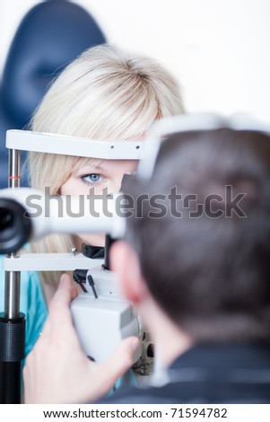 optometry concept - pretty young female patient having her eyes examined by an eye doctor (color toned image)