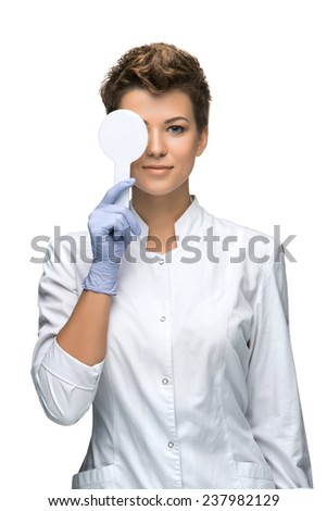 Optometry concept - pretty young woman having her eyes examined  isolated on white background