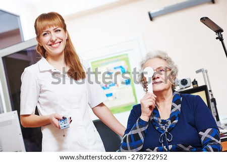 Optometry. female doctor ophthalmologist or optometrist helps to read senior woman during sight testing or eye examinations in clinic