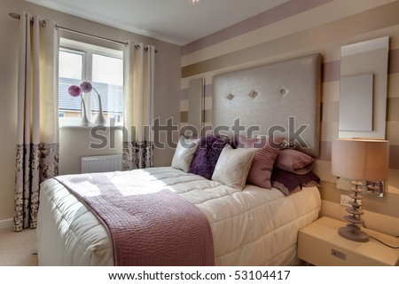 Opulent modern bedroom with fashionable oversized headboard and brightly colored fabrics
