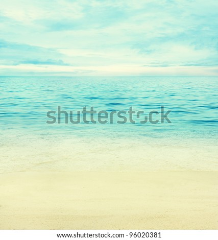 or spring abstract background. Golden sand with blue ocean and cloudscape and sunset in the back.