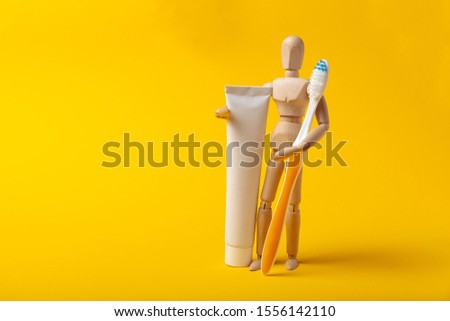 Oral hygiene and dental care. Wooden man holds toothbrush and toothpaste. #1556142110