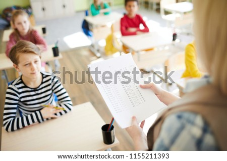 Oral questioning at math class: teacher holding paper with algebraic examples and asking pupils about solutions in classroom #1155211393