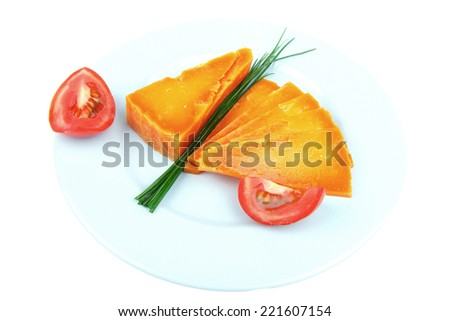 orange aged delicious cheddar cheese chop with slice on blue plate with tomatoes and chives isolated over white background stock photo
