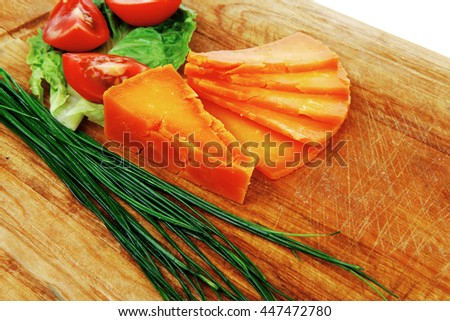 orange aged delicious cheddar cheese chop with slice on wooden plate with tomatoes , chives and salad . isolated over white background stock photo