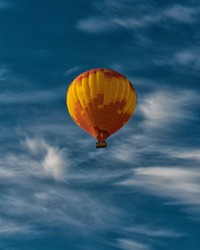 Orange air balloon in blue sky. Colorful image for backgrounds, wallpapers. Freedom of movement. Human rights.