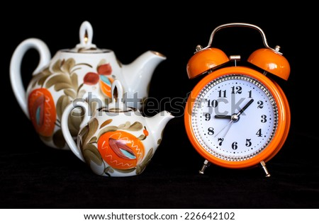 Orange alarm clock and decorative tea pots beside on black velvet texture background.  Tea time. Colorful lifestyle. Modern stylish design