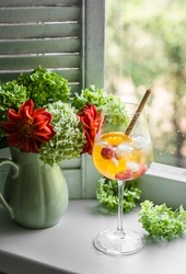 Orange alcohol ice cocktail and a bouquet of summer garden flowers in a vintage ceramic vase on the window on a summer day