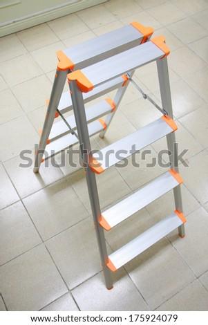 orange aluminum folding ladder, stepladder on tile floor for general repair