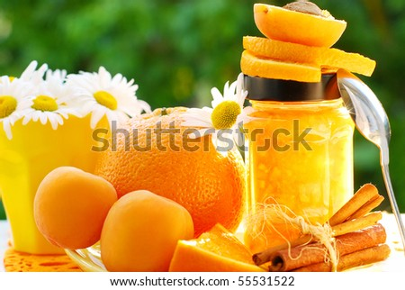 orange and apricot jam in jar on garden table