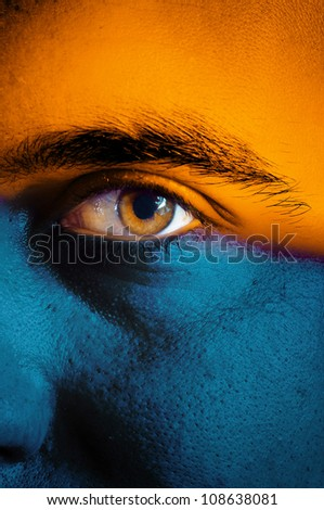 Orange and blue flag painted on face of a sport team supporter, close up of a male eye.