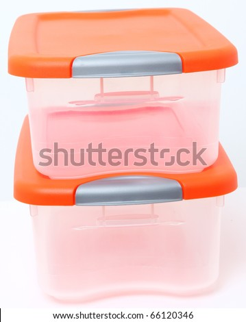 Orange and clear plastic storage container bins stacked over white background. - stock photo