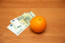 Orange and euro. The table is orange. 2 banknotes, new and old design. The 2002 and 2013 euro design. The past and the present. Pay for food, fruit. It contains a lot of vitamin C. The focus is on the
