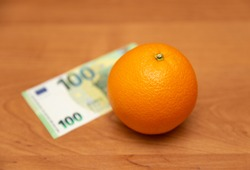 Orange and euro. The table is orange. 100 euro banknote. The 2013 design. A fruit. It contains a lot of vitamin C. The focus is on the orange.