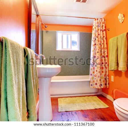 Orange and green bathroom with tub, sink  and wood floor.