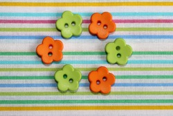 Orange and green flower-shaped buttons on striped cotton fabric close-up. Spring mood.