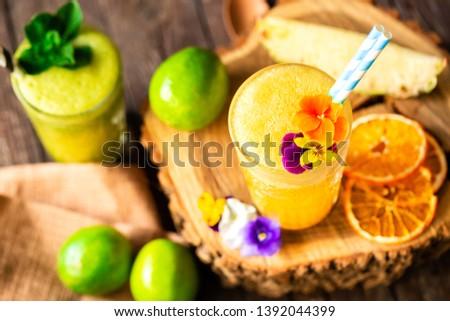 Orange and green refreshing fruit smoothie beverages served on the wooden stump, natural beverage decoration  #1392044399