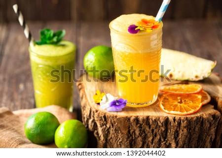 Orange and green refreshing fruit smoothie beverages served on the wooden stump, natural beverage decoration  #1392044402