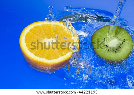 Orange and kiwi with splashing water. Tropical citrus fruit
