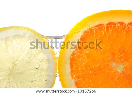 Orange and lemon slices in water with air bubbles on white background