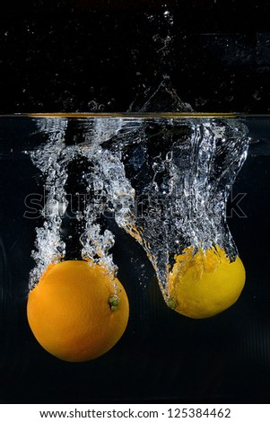 Orange and lemon splash on black background