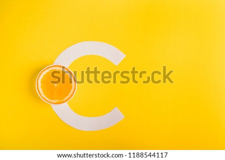 Orange and letter C on a yellow background. Concept of Vitamin S.  Immunity protection concept, antiviral prevention. Protection against colds, antioxidant