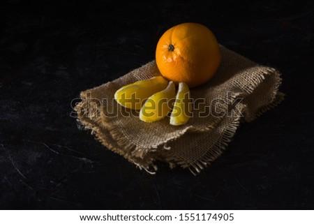 orange and orange segments on canvas. dark background. health concept.