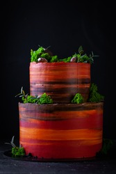 Orange and red colored .bunk cake with green grass decoration on the black background. Birthday cake for a boy