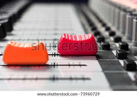 Orange and  red slider on a sound mixer with blurry background