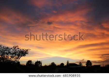 Orange and red sunset monsoon clouds over the back lit silhouette desert sky line in the Tucson Arizona desert  #681908935