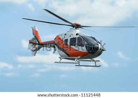 Orange and silver coloured helicopter flying above