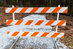 Orange and white striped plastic barriers on metal frame at road construction site. Sign blocks access to gravel road, under construction