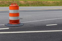 Orange and white striped traffic safety barrel on an asphalt street, road construction zone, horizontal aspect