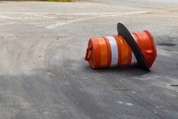 Orange and white traffic barrel knocked over on its side, traffic accident reckless driving, horizontal aspect