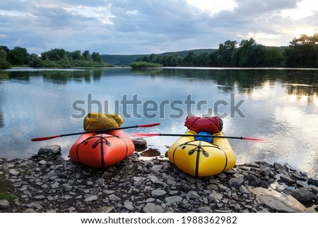 Orange and yellow packrafts rubber boats with padles ready for adventures on a sunrise river. Packrafting. Active lifestile concept Stock fotó ©