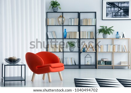 Orange armchair next to table in bright living room interior with bookshelf and poster on white wall