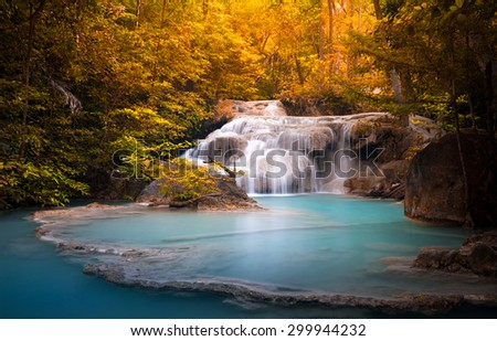 Orange autumn leaves of wild dense forest and scenic waterfall falls in natural blue water pond #299944232