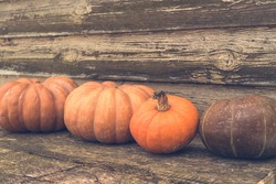 Orange autumn pumpkins on the old rustic table with vintage film colours background