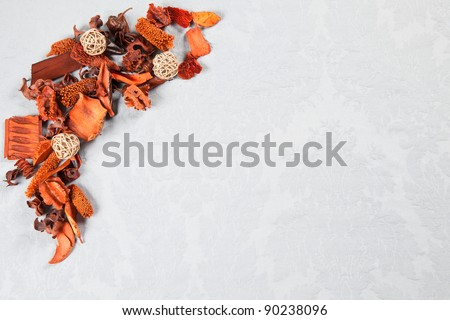 Orange autumnal decorations of dried flowers over light blue Damask pattern great for greeting cards