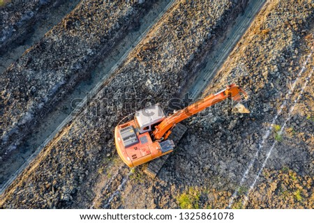 orange bachkhoe is digging soil creating  grooves for planting parm and coconut farmland agricultural in Thailand aerial view