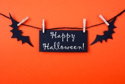 Orange Background with a Black Label and two Bats on a Line with Happy Halloween on it