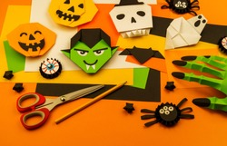 Orange background with collection of Halloween objects overhead view. Skull, pumpkin, ghost, monster, green hand, spider, bat, witch, feared party decor. Handwork.