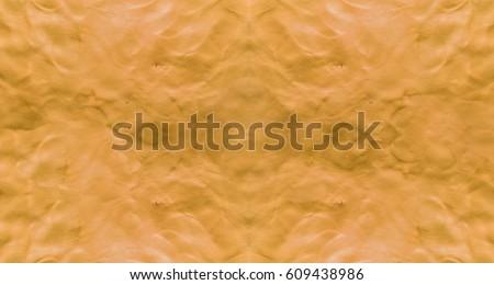 Orange background with fingerprints made from plasticine.