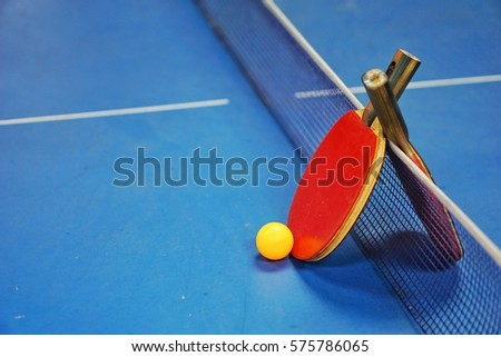 Orange ball with a table tennis racket red and black on a blue table with blurred background, indoor games #575786065